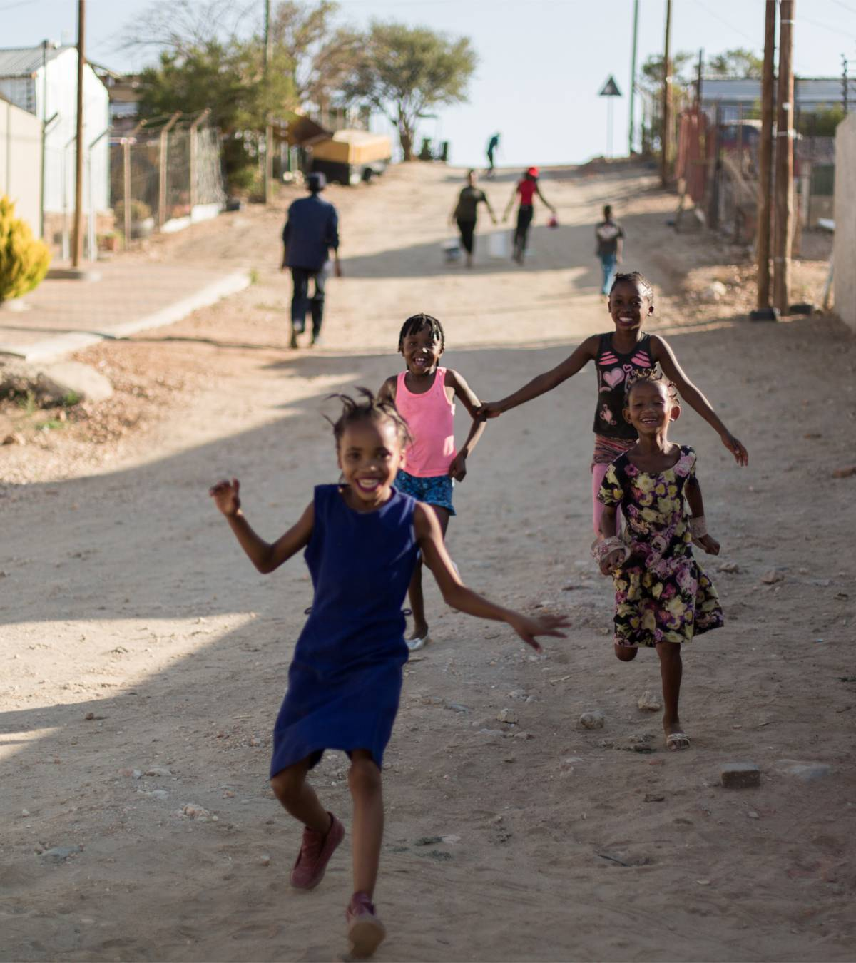 Four children running down a street, smiling